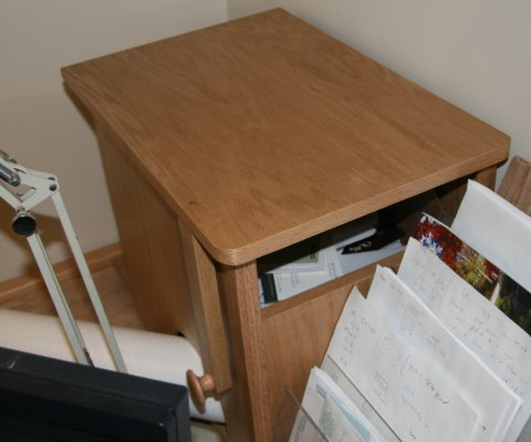 In back corner of desk, a wooden box with slot for throwing papers.